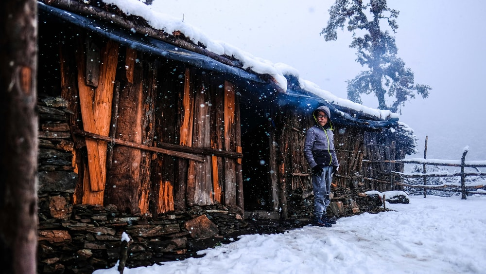 man standing in front of wooden house