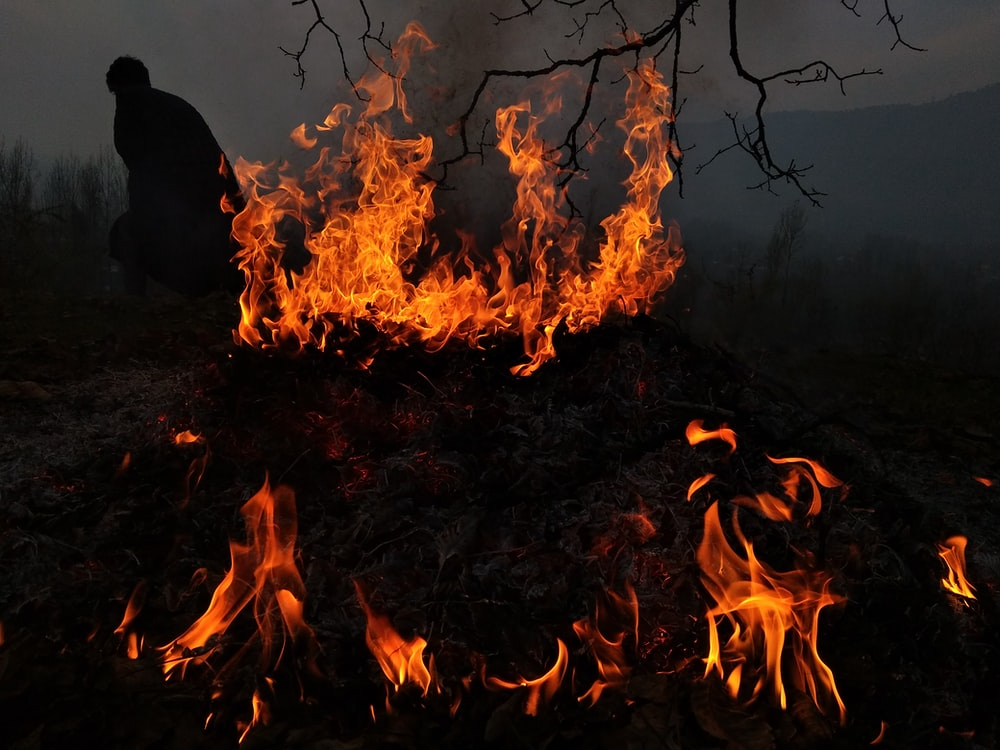silhouette of person standing near the fire