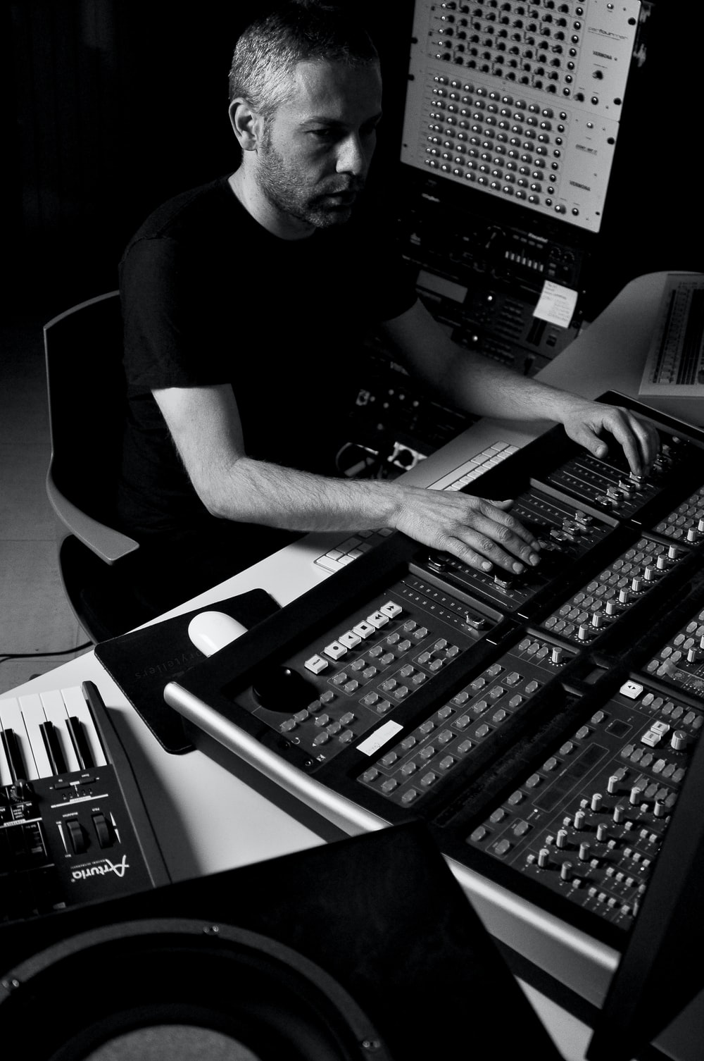 man using audio mixing console grayscale photo