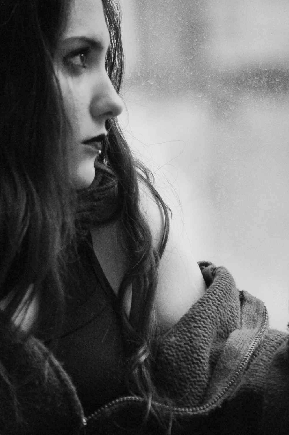 grayscale photography of woman looking upward near window