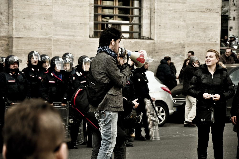 man holding megaphone front of woman