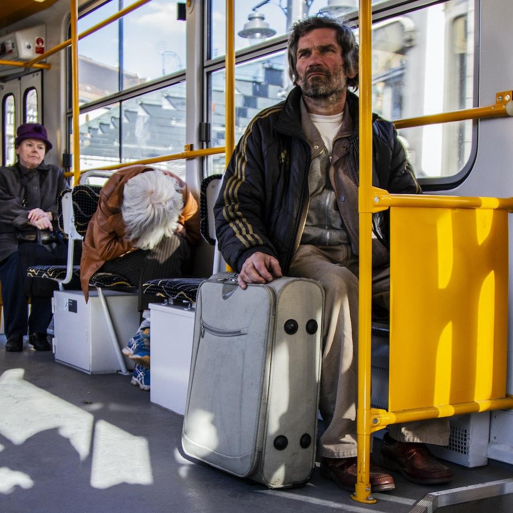 man sitting down beside luggage