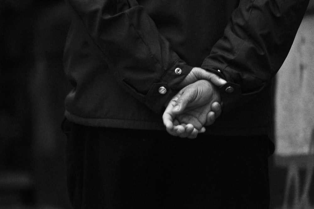 gray scale photo of holding hands