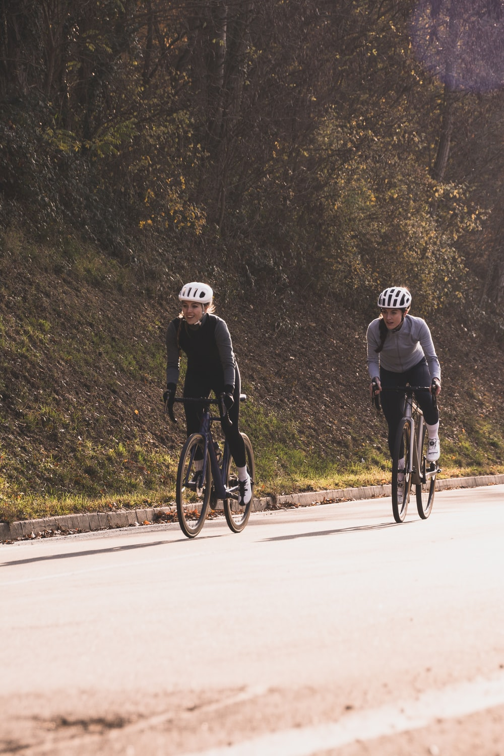 two people riding on bike uphill