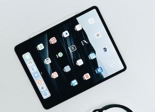flat lay photo of black iPad and corded headphones