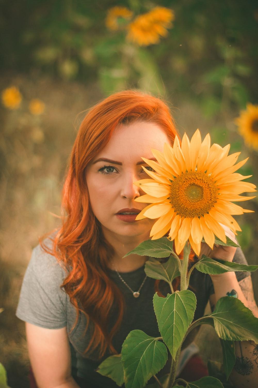 selective focus photo of woman sitting near sunflower
