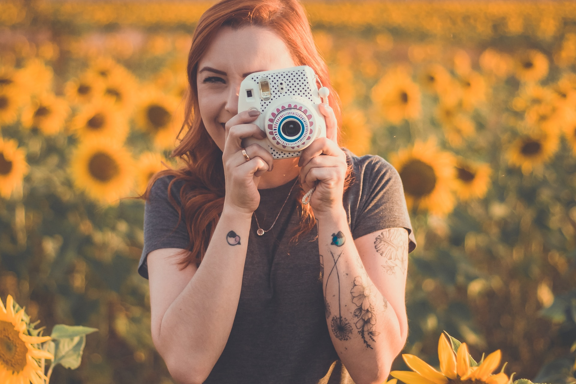 woman holding white instant camera standing on meadow of Sunflowers