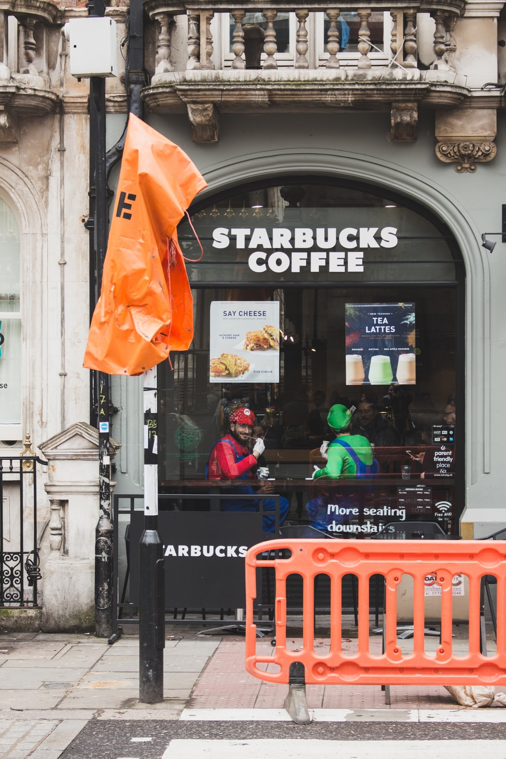 two men with Super Mario and Luigi costumes sitting inside Starbucks coffee cafe