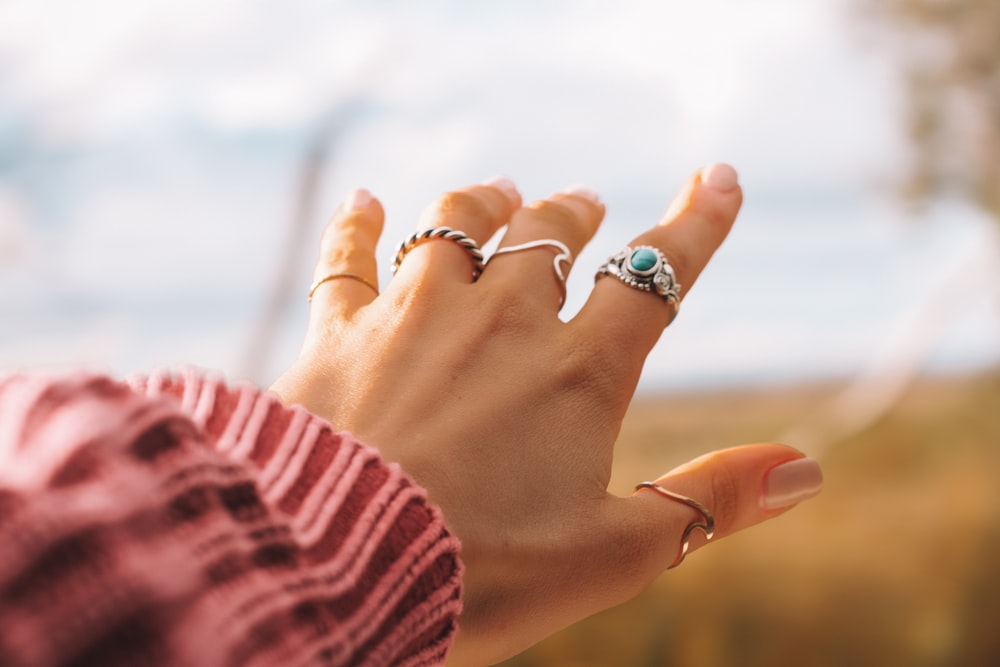 selective focus photo of person's hand with five rings