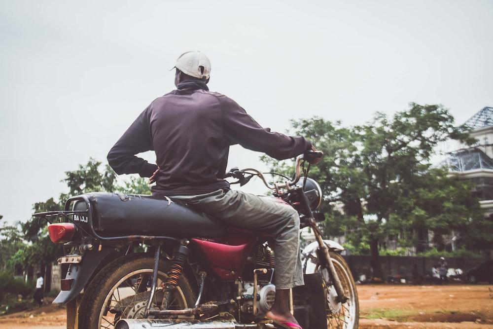man riding black standard motorcycle