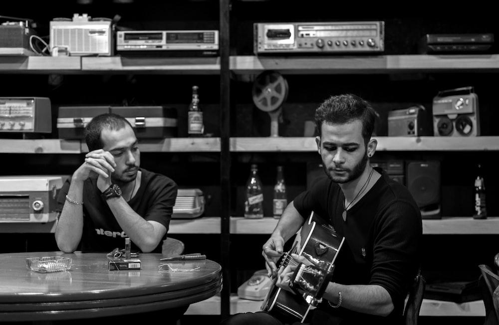 man wearing black shirt playing guitar