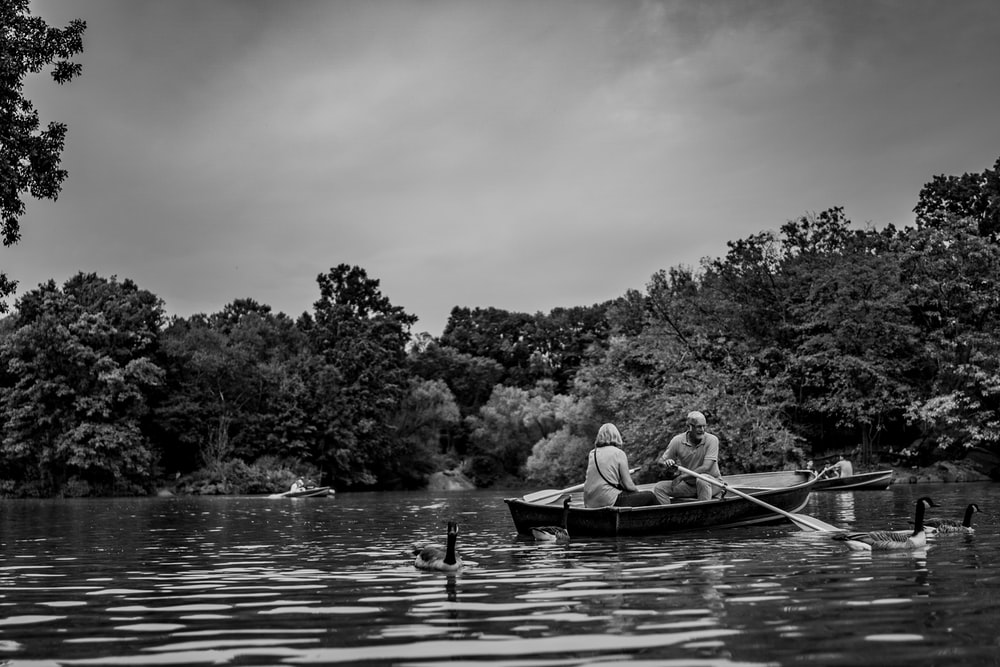 grayscale photography of woman and man riding on boat