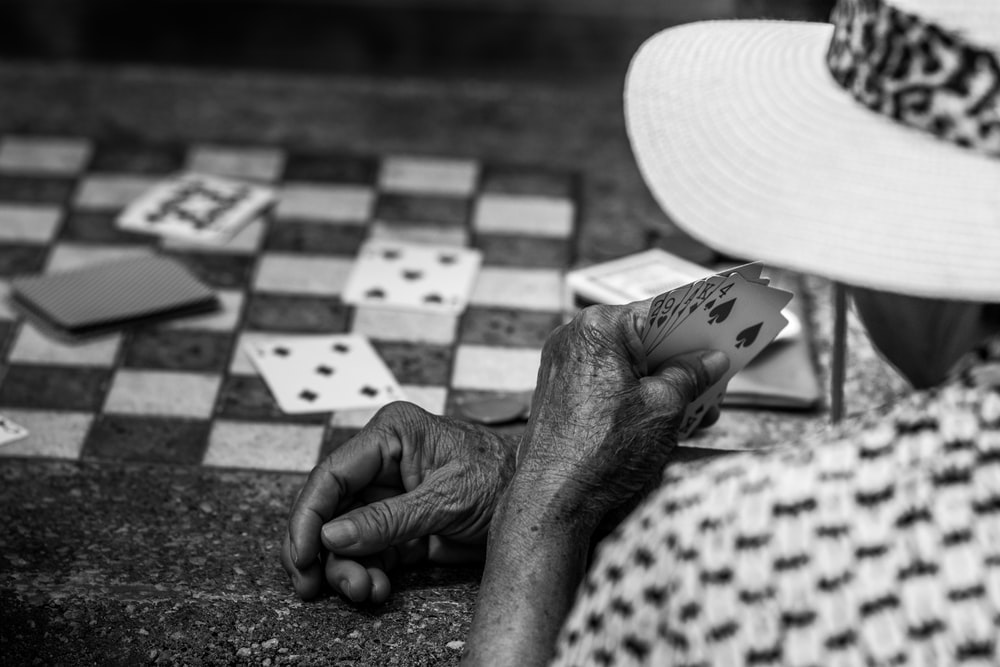 grayscale photo of person playing cards