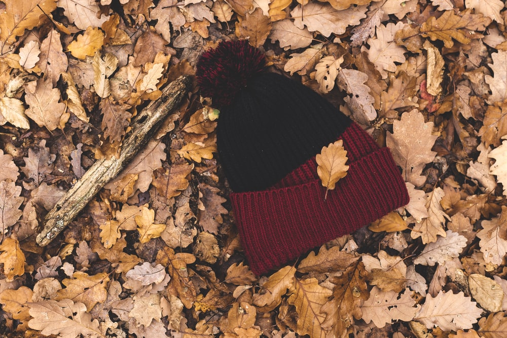 red and black bobble hat on ground