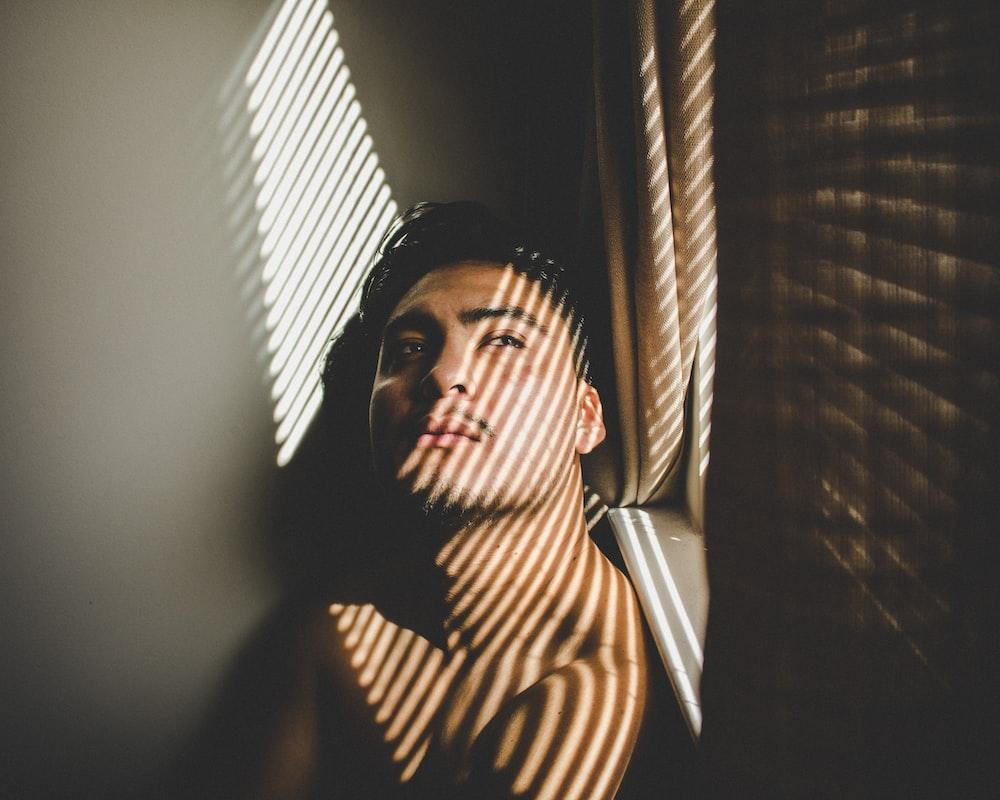 man leaning beside window