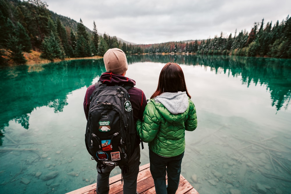 man and woman standing near body of water