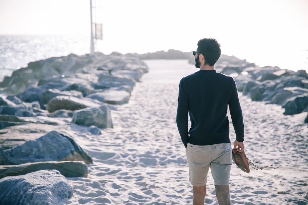 man standing beside rocks