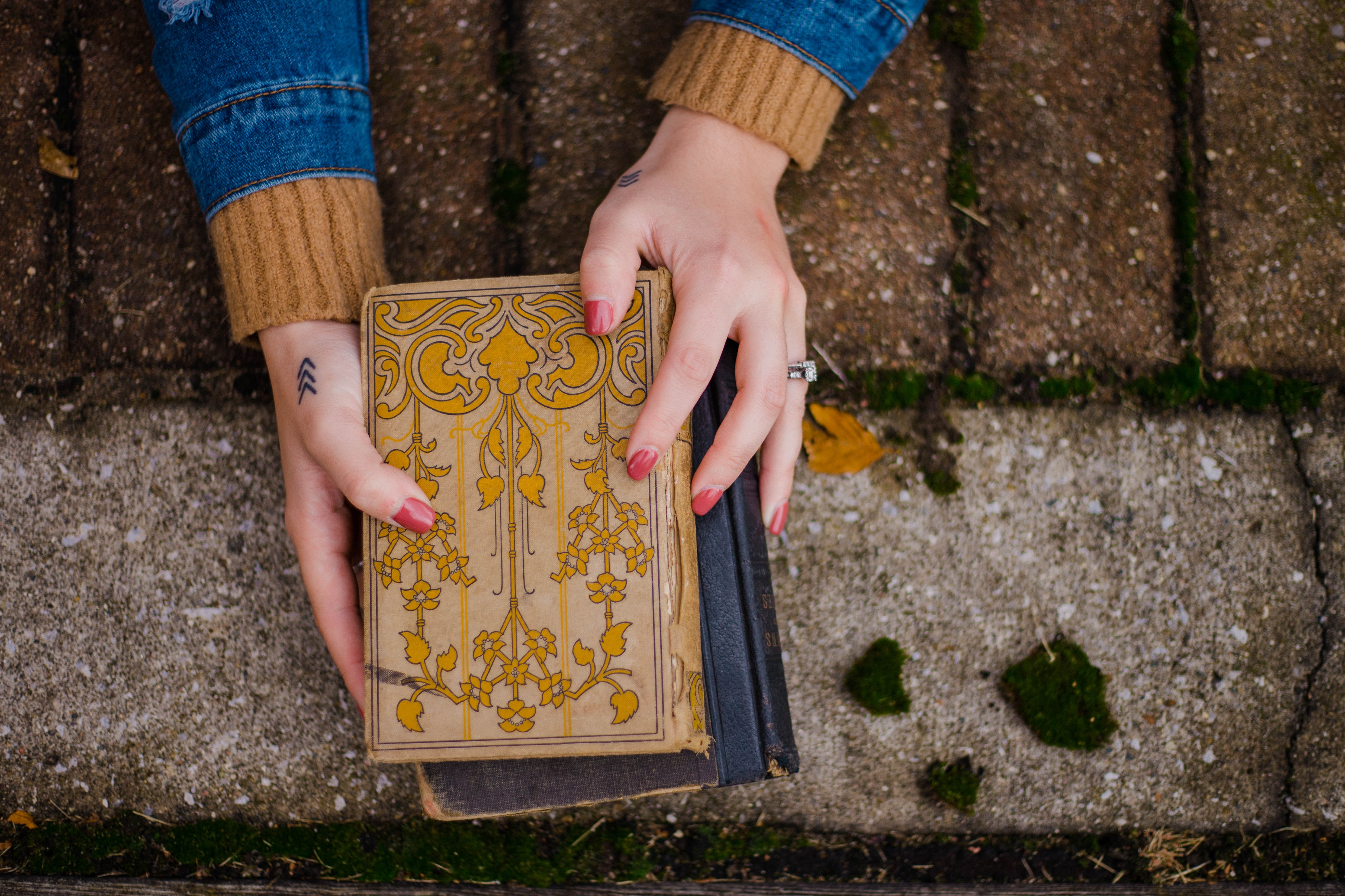 person holding beige and black books