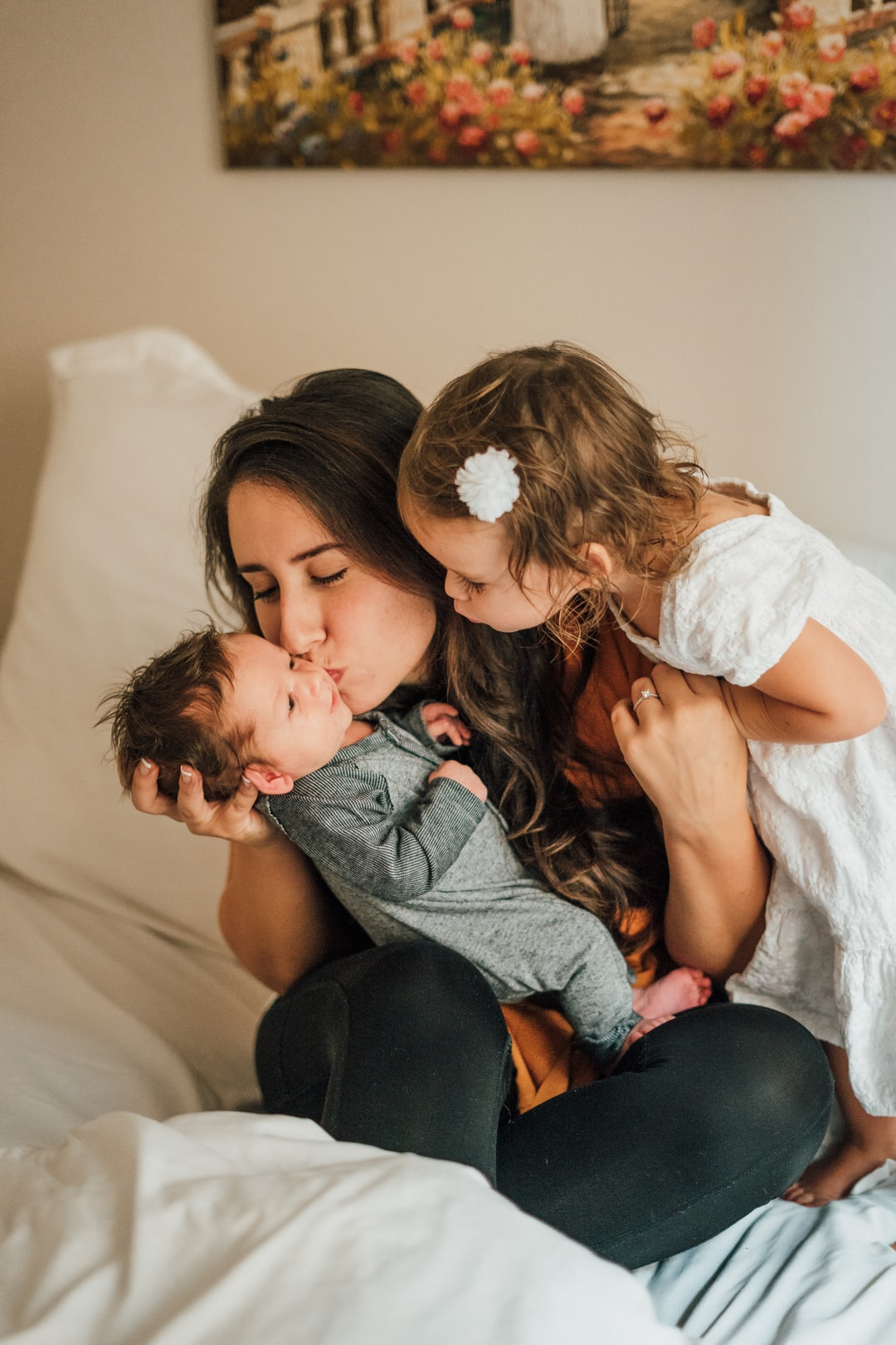 Mother kissing baby boy with young daughter on bed