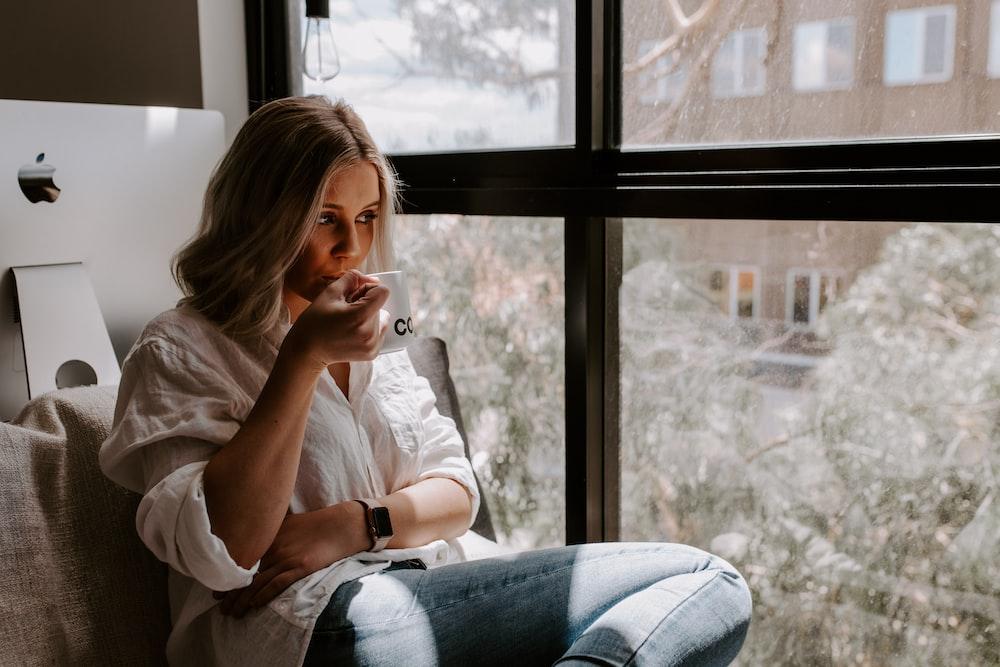 woman holding white mug sitting beside window