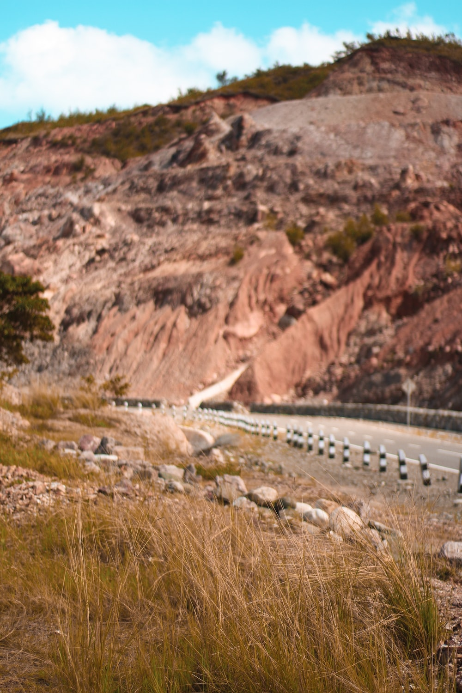 brown road beside rocky mountain