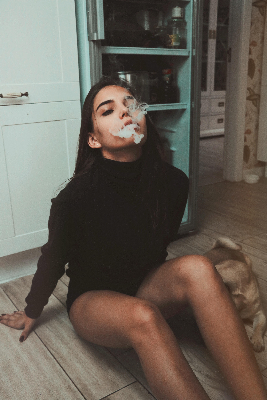 woman sitting on floor while smoking