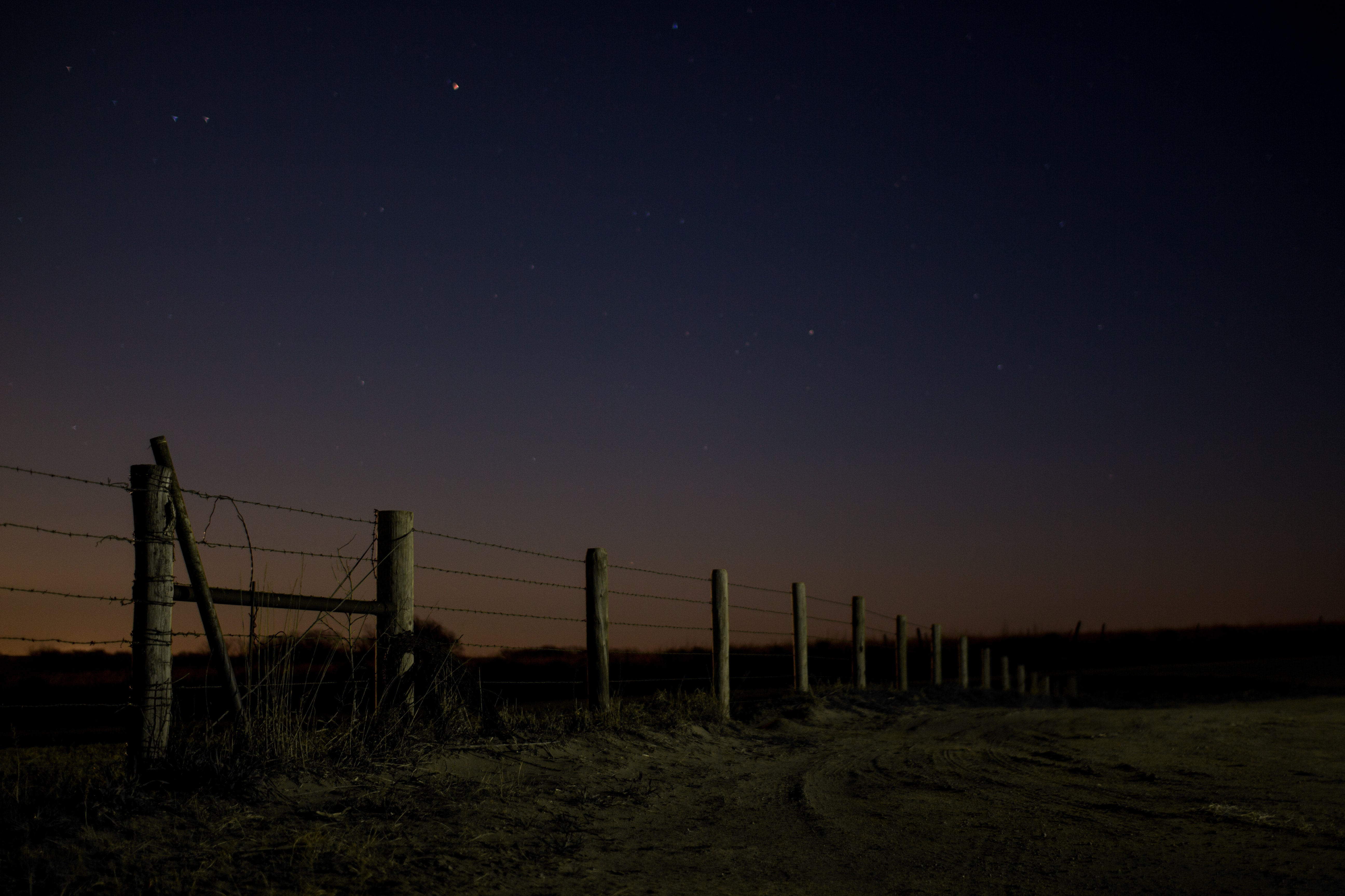 landscape photo of pole and wire fence during nighttime