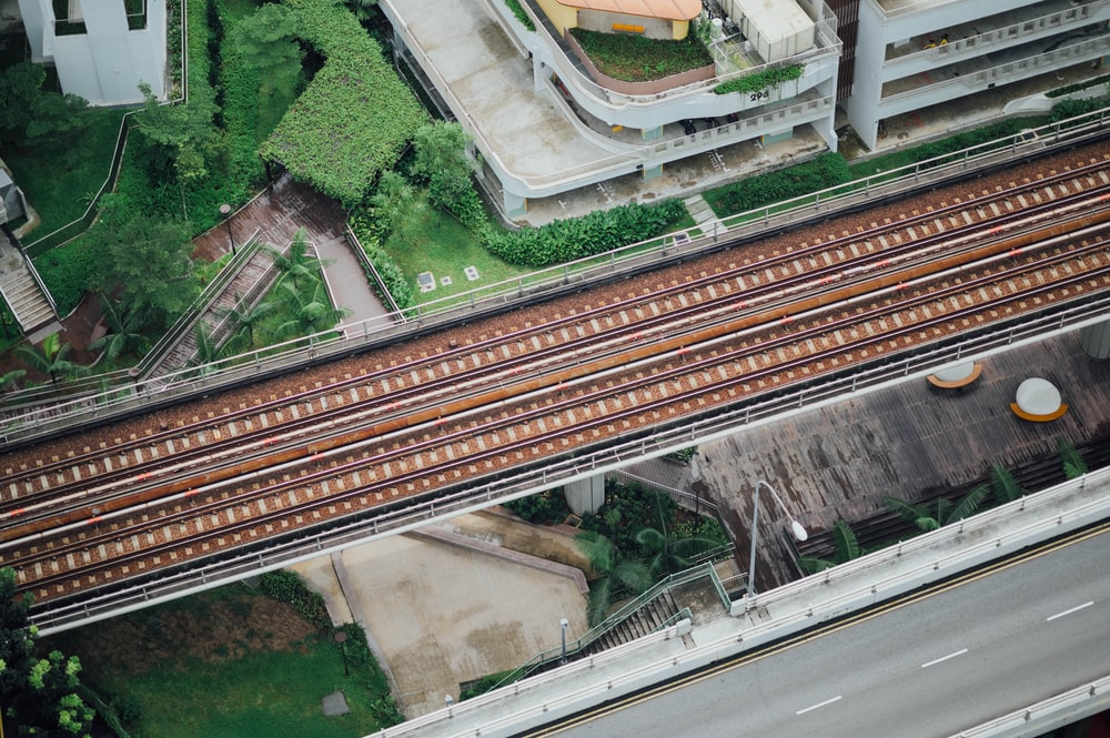 aerial photography of train rails between bridge and building