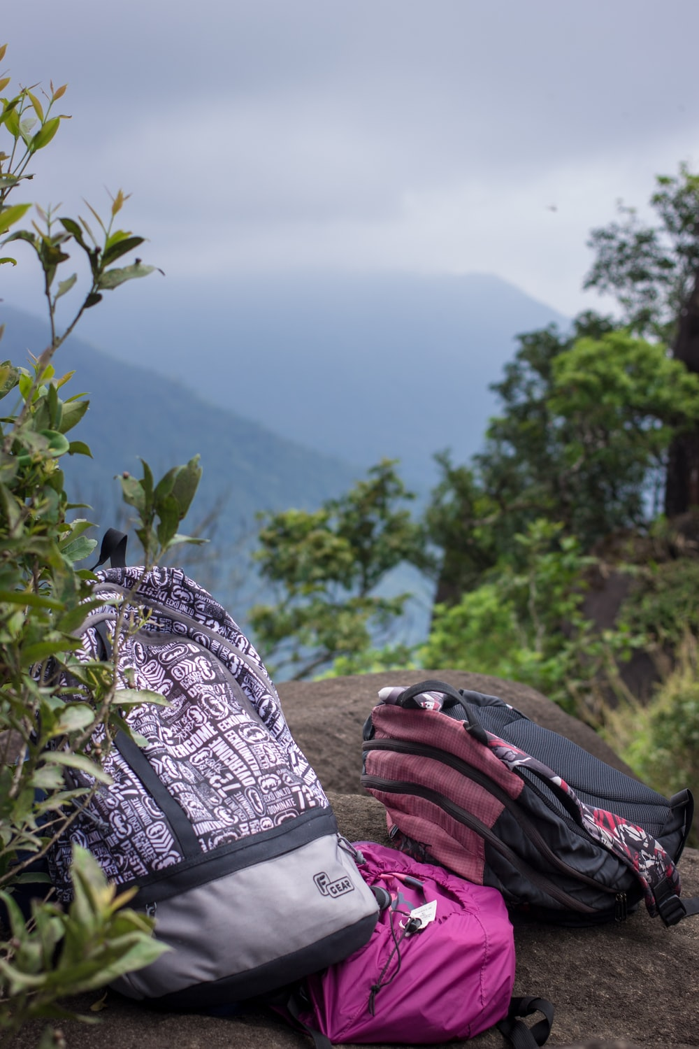 three backpacks on gray rock under cloudy sky during daytime