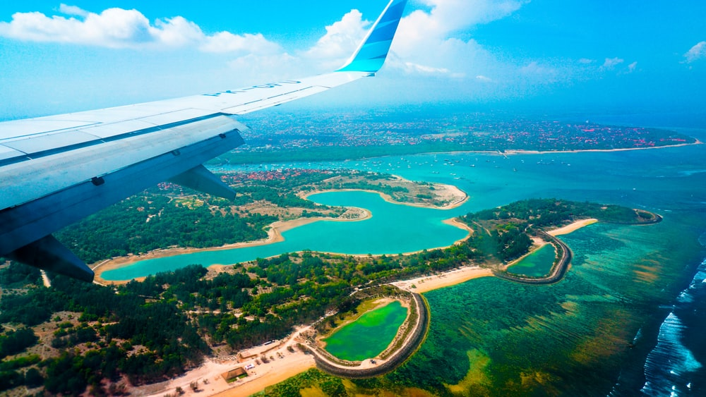 person inside airplane flying at high altitude with view of island during daytime