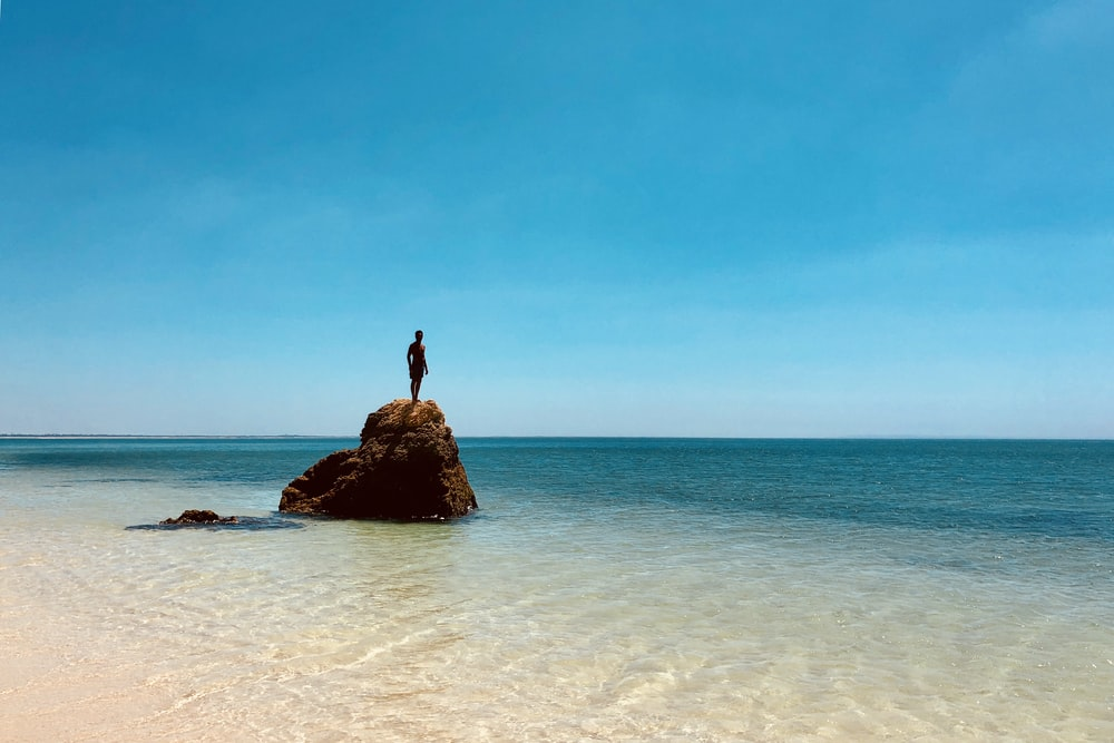 person standing on top of rock across sea during daytime