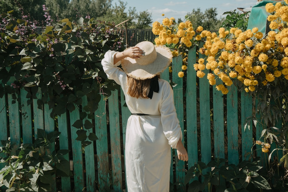 woman facing wooden fence with crawling vine and flowers