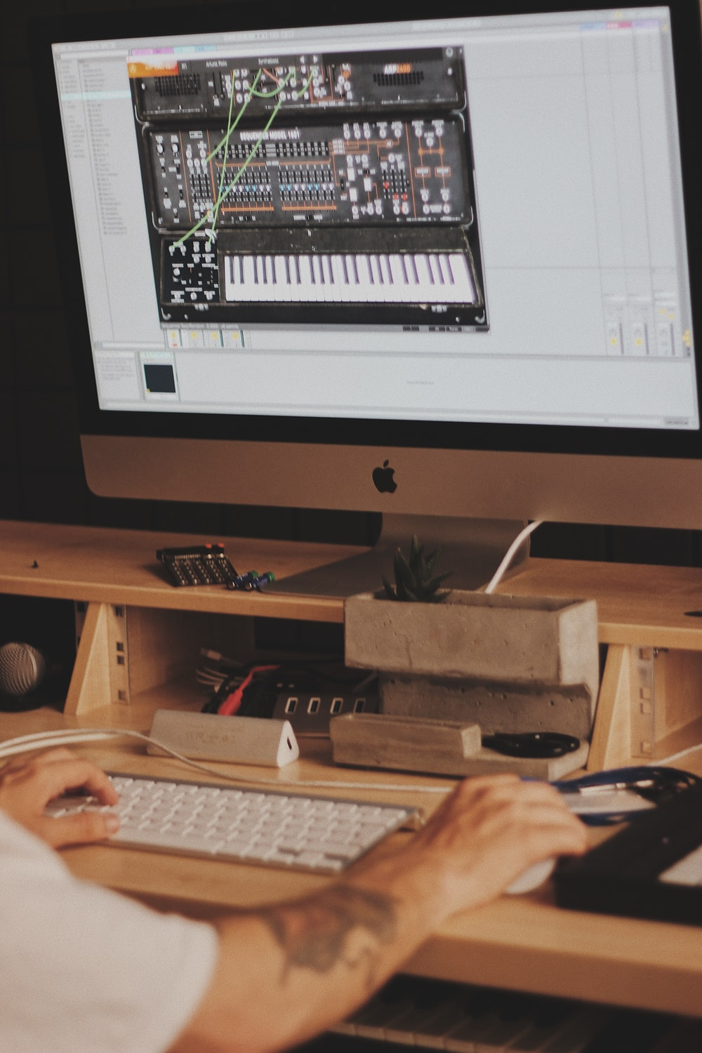 person using iMac computer set with digital piano application