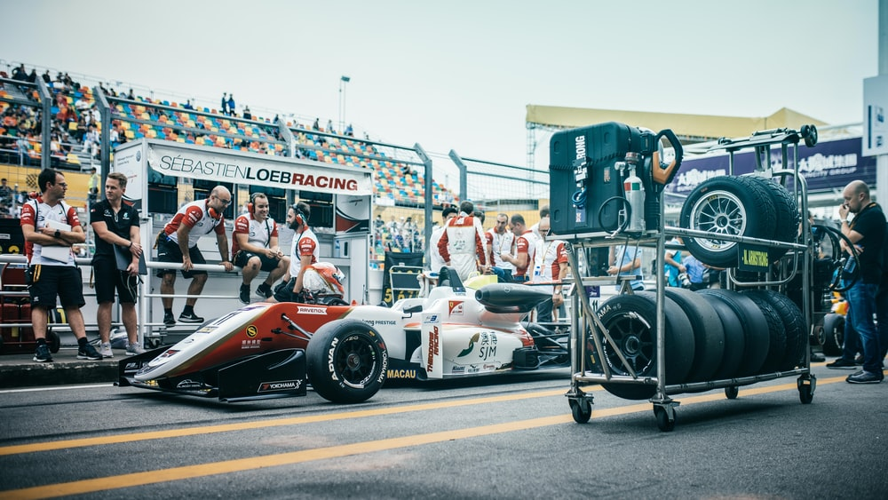 white and red Formula 1 car at pit stop with crew during daytime