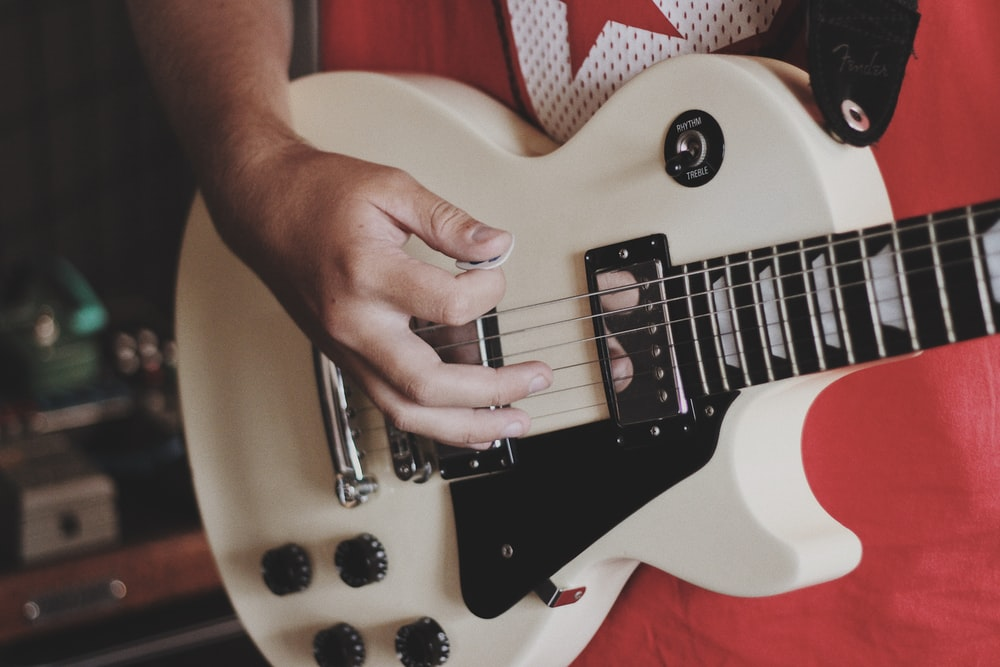 person playing white and electric guitar
