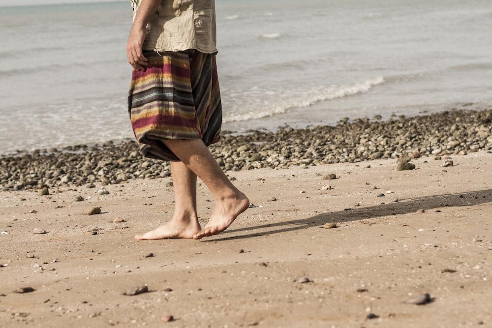 person walking on seashore
