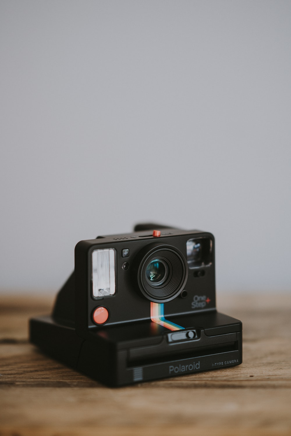 black instant camera on wooden surface