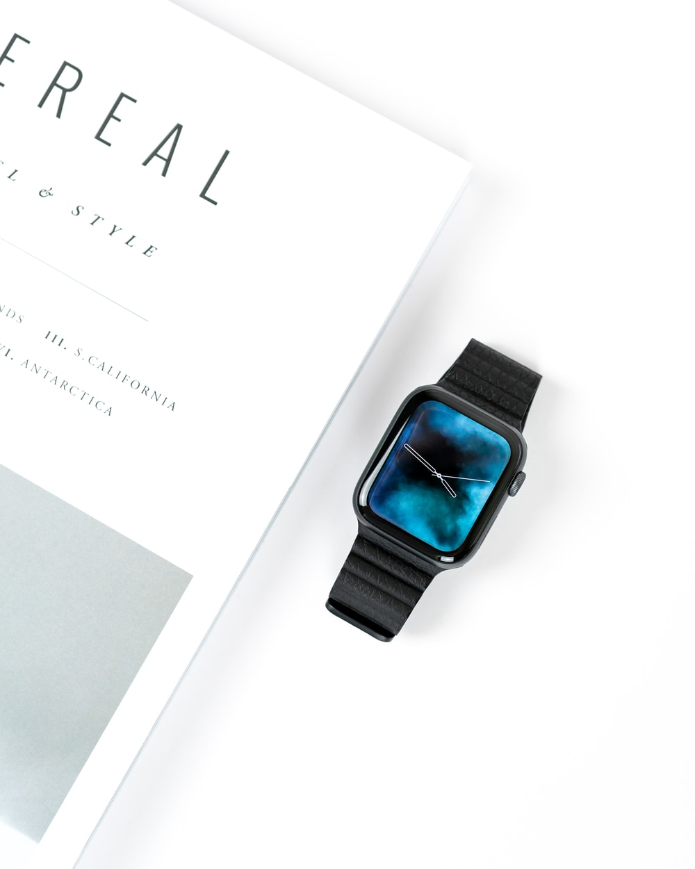 black smart watch beside white book