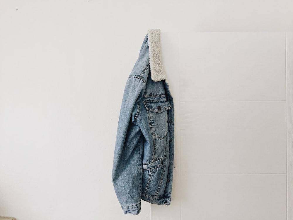 blue washed jacket hanging on white door