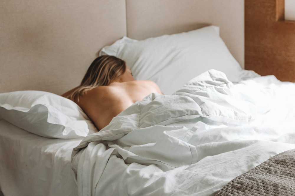 naked woman lying on bed during daytime