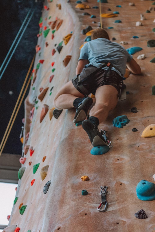 man rock climbing inside climbing area at daytime