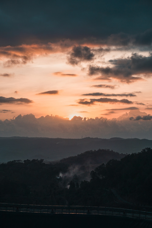 mountain under orange and gray skies view