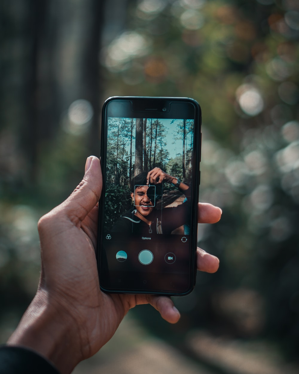 person holding black smartphone while taking selfie under the tree