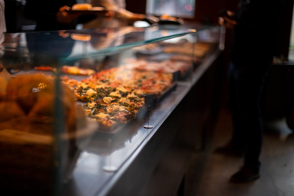 selective focus photography of food inside clear glass display cabinet