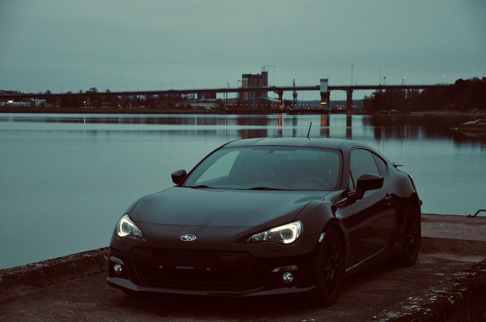 parked black coupe under gray skyu