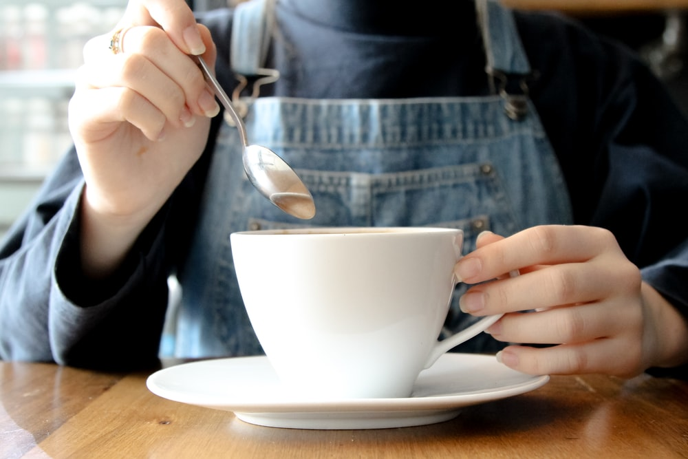 person having coffee during daytime