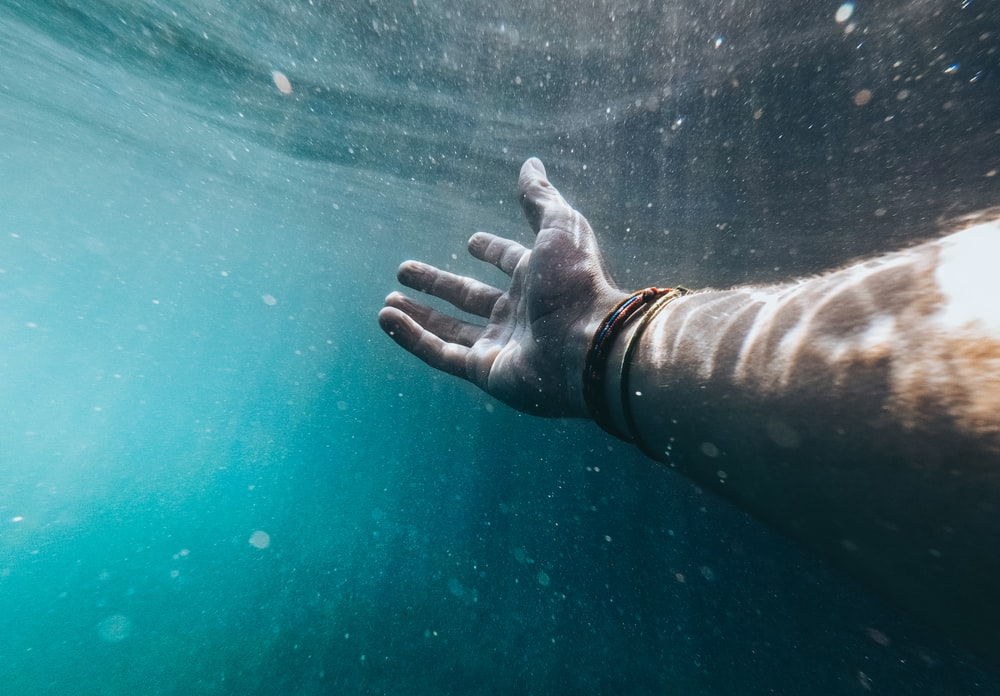person showing right hand with bracelets in body of water