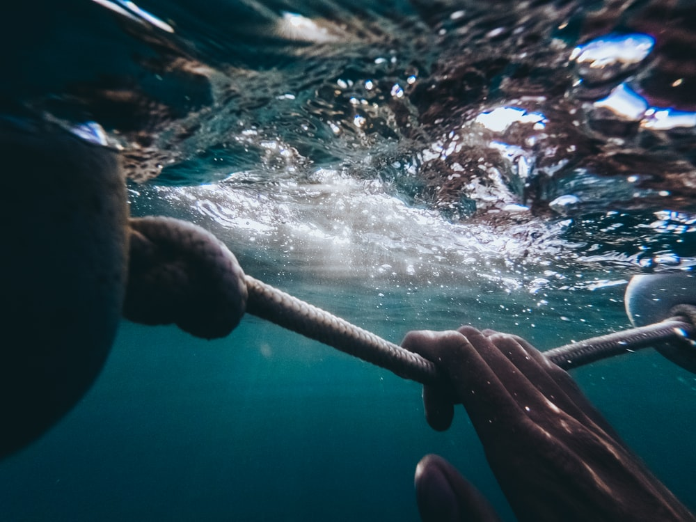person holding rope under water