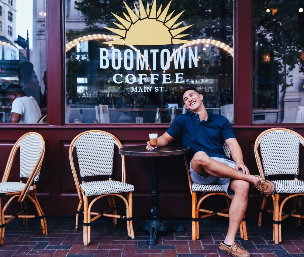 man sitting on wicker chair beside table outside Boomtown Coffee bar at daytime