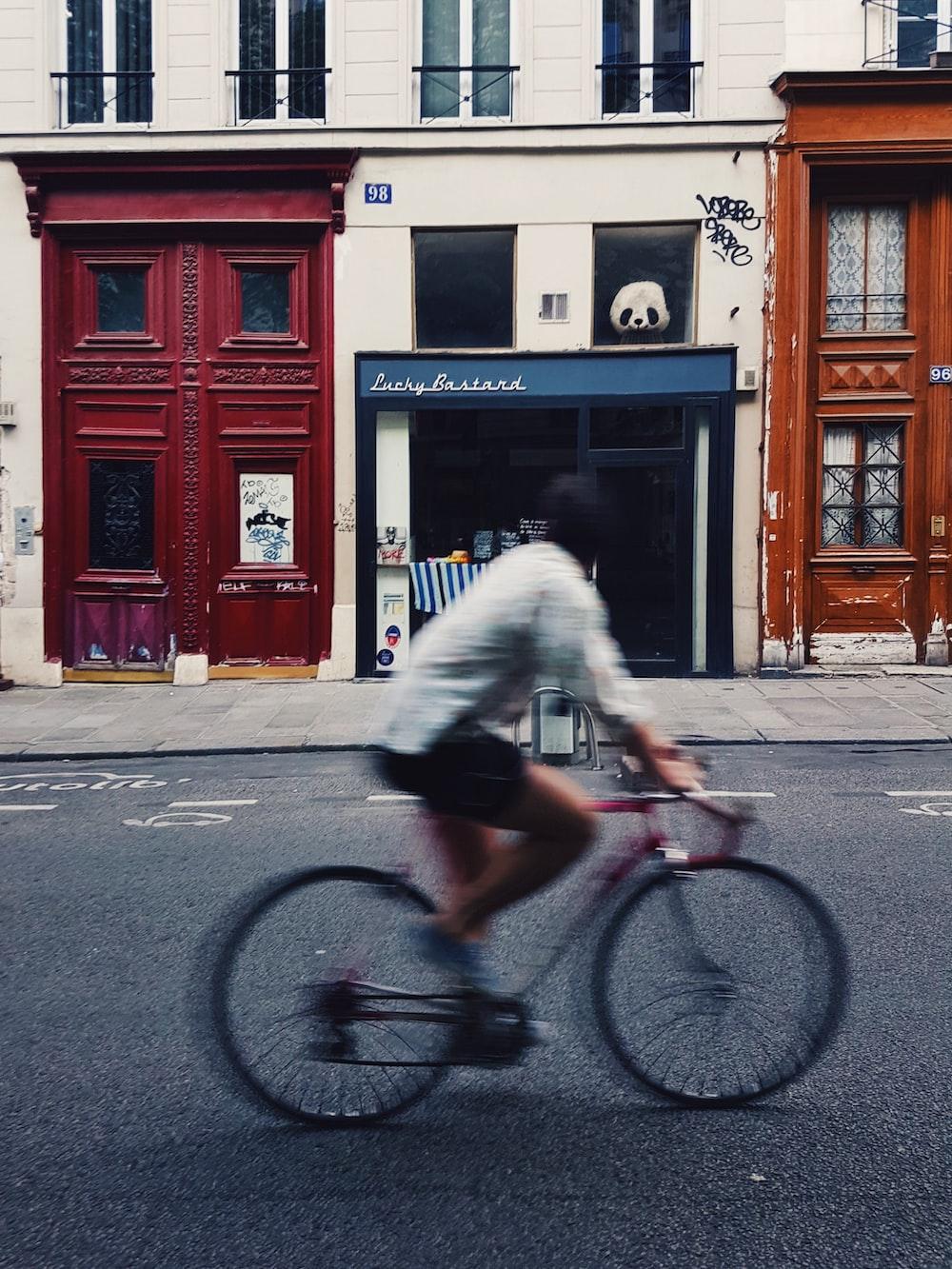 man riding on pink bicycle
